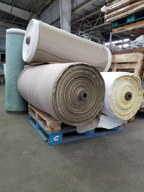 Photo of large fabric rolls with nearby pallets