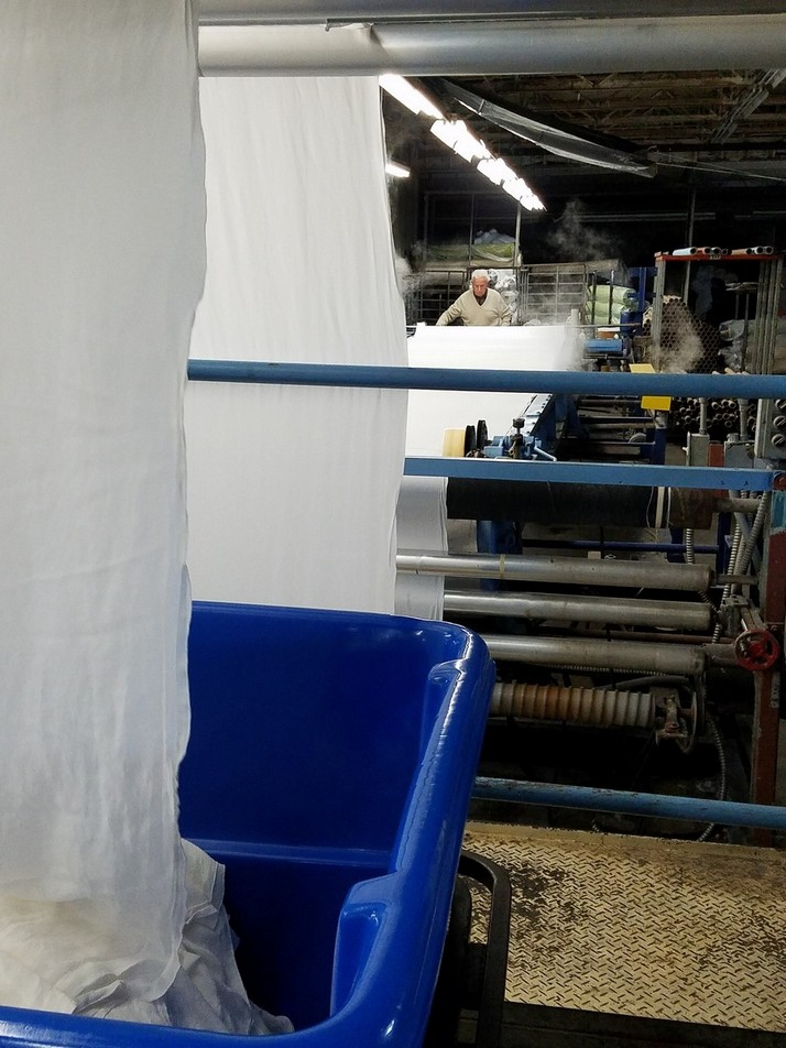 Photo of process finishing equipment with man in background